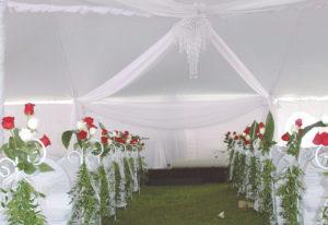 Allée des mariée banc décoré avec des fleurs roses et blanches et un lustre au plafond, avec chapiteaux CDQ