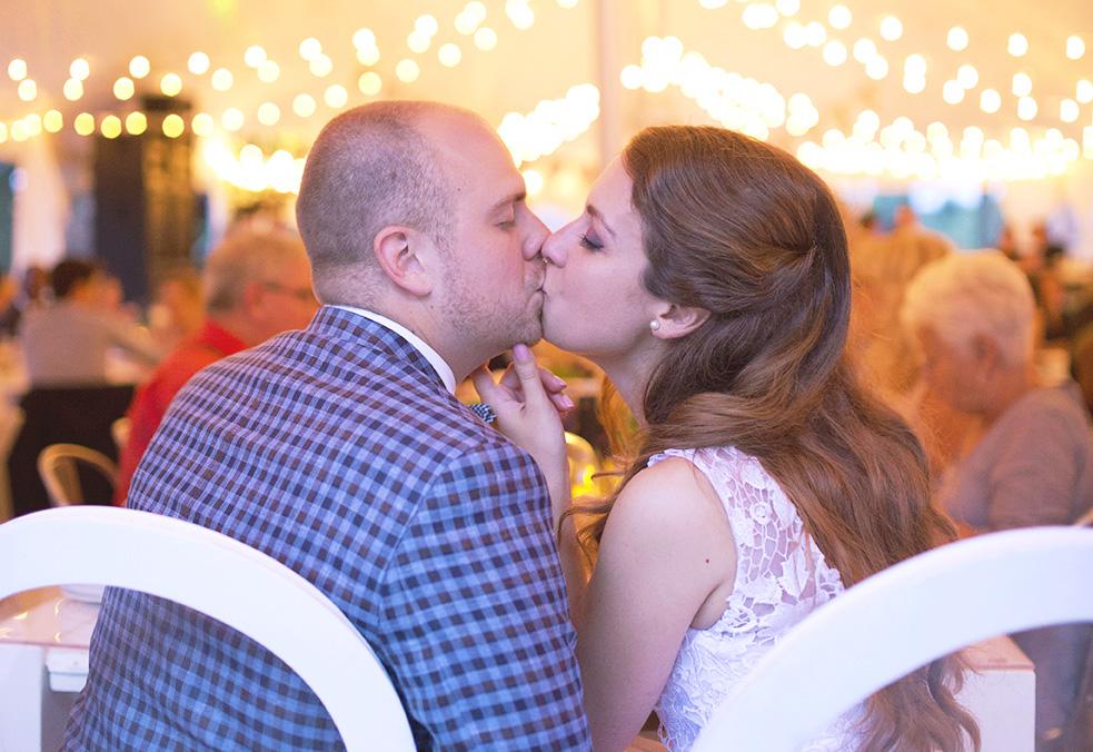 Mariés qui s'embrasse à leur table sous le chapiteaux CDQ